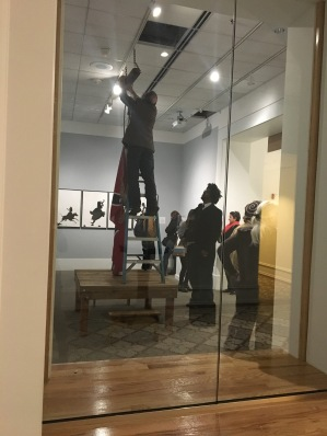 Artist John Sims supervises the installation of his work The Proper Way to Hang the Confederate Flag in the Museum after a public redress on campus.